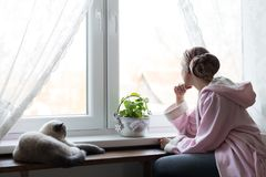 Young adult female cancer patient wearing headscarf and bathrobe sitting in the kitchen with her pet cat. Young adult female cancer patient wearing headscarf Royalty Free Stock Image