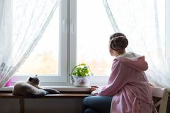 Young adult female cancer patient wearing headscarf and bathrobe sitting in the kitchen with her pet cat. Young adult female cancer patient wearing headscarf Stock Photos