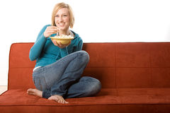 Young Adult Female on Couch. Young adult blond female model sits on orange colored couch eating popcorn from a bowl Royalty Free Stock Images