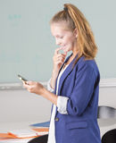 Young adult female holding cellphone in office stock images