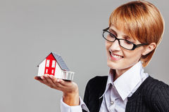 Young adult female holding a model house and looking to it Royalty Free Stock Image