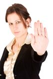 Young adult female motioning to stop. Brunette business woman holding hand up, looking annoyed. Hand in focus, face out of focus Royalty Free Stock Photos
