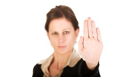 Young adult female motioning to stop. Brunette business woman holding hand up, looking annoyed. Hand in focus, face out of focus Royalty Free Stock Images