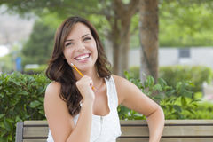 Young Adult Female Student on Bench Outdoors Stock Image