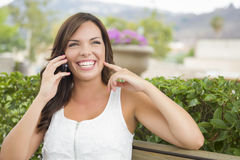 Young Adult Female Talking on Cell Phone Outdoors on Bench Royalty Free Stock Image