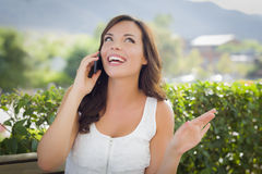 Young Adult Female Talking on Cell Phone Outdoors on Bench Stock Photo