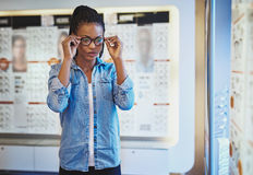 Young adult female testing the fit for eyeglasses Stock Image