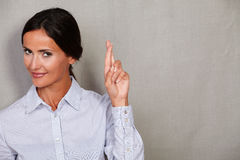 Young adult female wishing and crossing fingers Royalty Free Stock Image