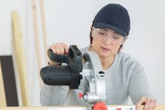 Young adult female woodworker cutting board in workshop royalty free stock photography