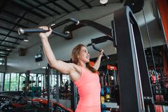 Young adult fitness woman doing pull ups. In pull up bar stock photo
