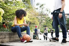 Young adult friends chilling at the park using smartphones and s. Kateboarding youth culture concept stock photo