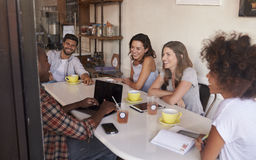 Young adult friends hanging out in cafe, seen through window Stock Photo