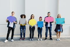 Young adult friends holding up copy space placard. Thought bubbles royalty free stock photo