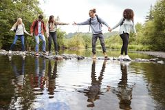 Young adult friends reaching to help each other cross a stream balancing on stones during a hike royalty free stock image