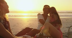 Young adult friends relaxing on the beach at sunset 4k