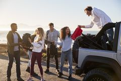 Young adult friends unloading backpacks from the back of car stock photography