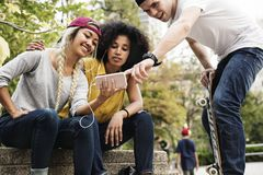 Young adult friends using a smartphone. And listening to music outdoors royalty free stock photography