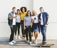 Young adult friends using smartphones together. Outdoors youth culture concept stock images
