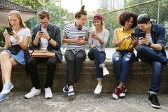 Young adult friends using smartphones together. Outdoors youth culture concept royalty free stock image