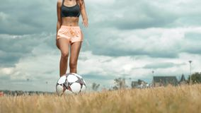 Young adult girl close up playing football or soccer, kicking a ball with her knee Beautiful brunette woman in a sports