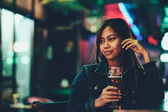 Young adult girl in a club drinking beer alone Stock Photos