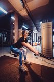 Adult girl doing suspension rope exercise together with her personal private coach. Young adult girl doing suspension rope exercise together with her personal Royalty Free Stock Image