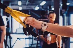 Young adult girl doing suspension rope exercise together with her personal private coach. Girl with a coach in the gym exercises her legs. closeup view Stock Photos