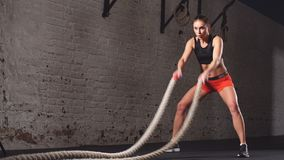 Young adult girl practising battle rope exercise during a cross fit workout at the gym,