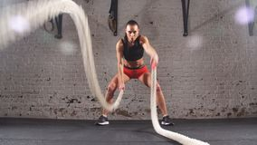 Young adult girl practising battle rope exercise during a cross fit workout at the gym, stock video