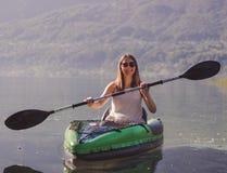 Young woman kayaking on the lake stock photo