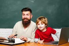 Young or adult. Happy family. Child learning. Preschool pupil. Man teacher play with preschooler child. Teacher and. Schoolboy using laptop in class royalty free stock image