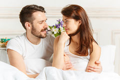 Young adult heterosexual couple lying on bed in bedroom Stock Image