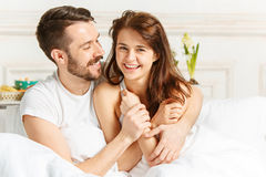 Young adult heterosexual couple lying on bed in bedroom. Young happy and smiling adult heterosexual couple sitting on bed in bedroom at home at morning royalty free stock image
