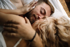 Young adult heterosexual couple lying on the bed in the bedroom. Pretty loving couple is luxuriating in bed together. They are hugging and smiling Royalty Free Stock Photos