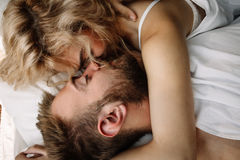 Young adult heterosexual couple lying on the bed in the bedroom Stock Photography