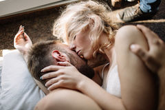 Young adult heterosexual couple lying on the bed in the bedroom Stock Image