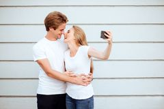 Young adult hipsters. boy and girl in white T-shirts smile and making selfie. stock photography