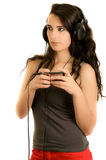 Young adult hispanic girl is listening to the music Stock Photo