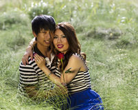 Young Adult Holding Each Other while sitting in Grass Field Stock Photography