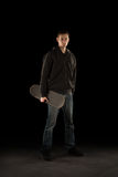 Young Adult Holding Skateboard. Tall casual urban young white Caucasian male holding a skateboard looking into the camera while standing Royalty Free Stock Image