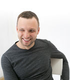 Young adult laughing man is sitting on a chair Stock Photography