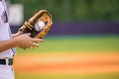 A young adult male baseball player holding a baseball glove and baseball ball in his glove.