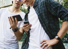 Young adult male friends on the basketball court using smartphones millennials concept royalty free stock photography