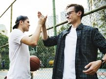 Young adult male friends playing basketball in the park royalty free stock photography