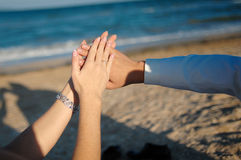 Young adult male groom and female bride holding hands on beach Royalty Free Stock Photo