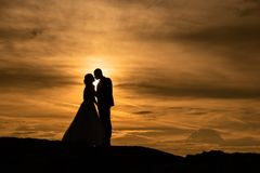 Young adult male groom and female bride holding hands on beach at sunset. Stock Photo