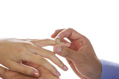 Young Adult Male hand putting engagement ring on Female finger Royalty Free Stock Image