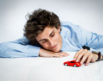 Young adult male plays with red toy car and having fun Royalty Free Stock Photo