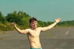 Young adult male shirtless outdoors. Young male adult with his arms out enjoying the sunshine shirtless on a warm summer`s day Royalty Free Stock Images
