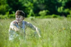 A young adult male sitting outside on a summer`s day. Young adult male sitting among long grass on a warm summer`s day Stock Photo